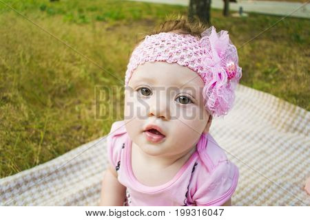 Newborn Girl In A Beautiful Park Outdoors, Lying On A Blanket And Looking At The Camera