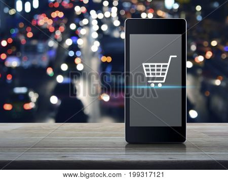 Shopping cart icon on modern smart phone screen on wooden table over blurred colourful night light city with cars Shop online concept