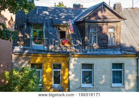 Flowery balcony and rood of old house at sunny day. Vilnius, Lithuania