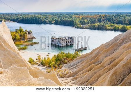 Sand hills of quarry with a pond and abandoned prison in Rummu, Estonia
