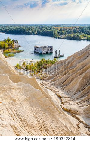 Sand hills of quarry with a pond and abandoned prison in Rummu, Estonia. Vertical shot