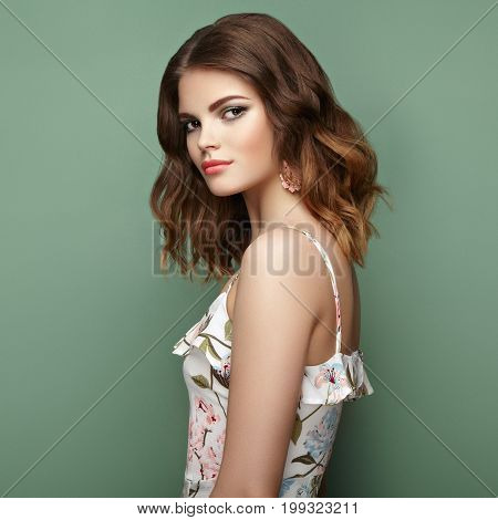Brunette young woman in floral spring summer dress. Girl posing on a green background. Summer floral outfit. Stylish wavy hairstyle. Fashion photo. Brunette lady