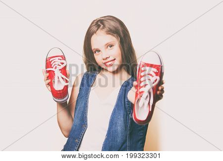 Young smiling girl with red gumshoes on white background poster
