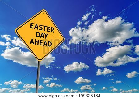 Background of blue sky with cumulus clouds and yellow road sign with text Easter Day Ahead