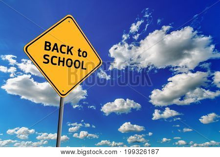Background of blue sky with cumulus clouds and yellow road sign with text Back to School