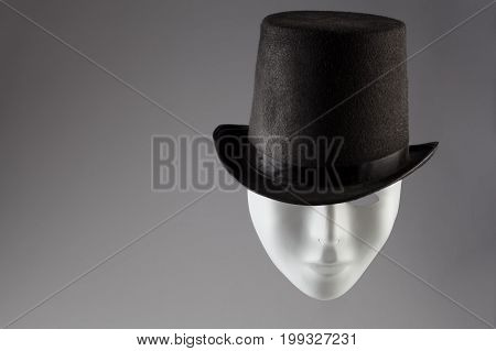 White mask wearing black top hat on gray background with copy space