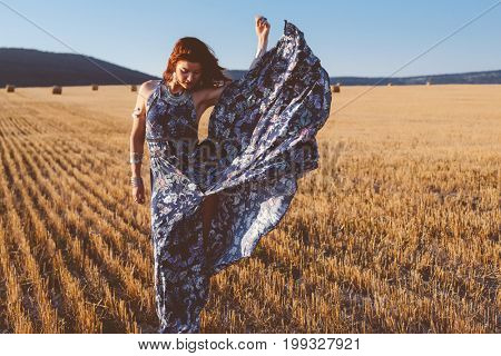 Beautiful model wearing summer cotton maxi dress and jewelery posing in autumn field with hay stack. Boho style clothing and jewelry.