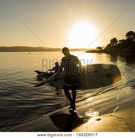 Sandy Bay beach Hobart Tasmania - 7 March 2014: men taking sit on top paddle boards for early morning paddle