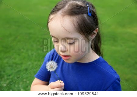 Little girl with dandelion in the park