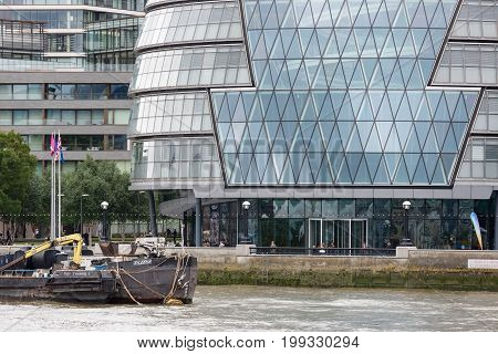LONDON ENGLAND - JUNE 08 2017: Modern office buildings along river Thames with moored barges in London England