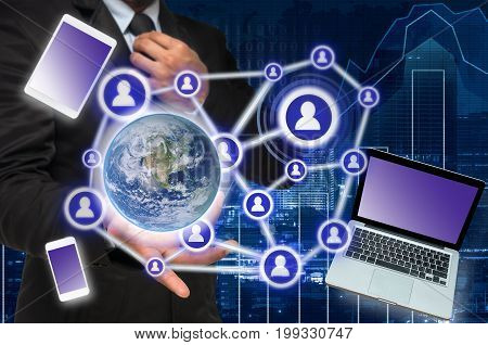 Businessman with show hand posture with the Social media and technology devide on trading graph with blurred cityscape background Elements of this image furnished by NASA Business network
