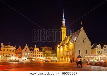 TALLINN, ESTONIA - 10 OKT 2015. Town Hall and Raekoja Square at night, walking and enjoying people