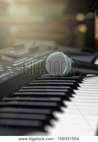 microphone on music keyboard with music brand blurred background music instrument concpet