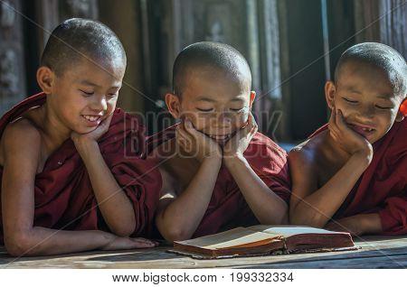 Three Buddhist novice reading at Shwenandaw pagoda mandalay myanmar