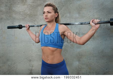 Young girl holds a barbell barbell on her shoulders