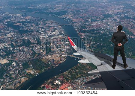 businessman standing on airplane wing which can see top view of cityscape Challenge business concept