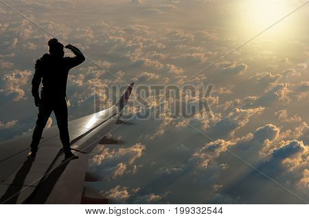 silhouette of man who looking the sun with clouds on airplane wing Challenge business concept