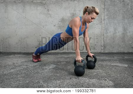 Young muscular girl doing push-ups from the floor and leaning on kettlebells