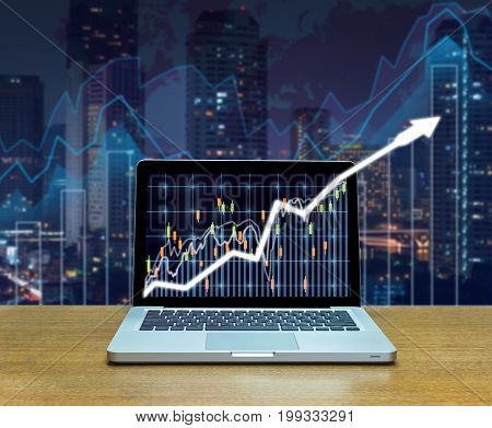 Stock exchange market trading graph over the screen of computer laptop on wood table over the photo blurred of trading graph background business marketing trade concept,