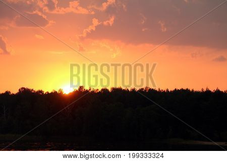 Thunderclouds sunset on forest and lake silhouette background. Nature summer sunlight wallpaper