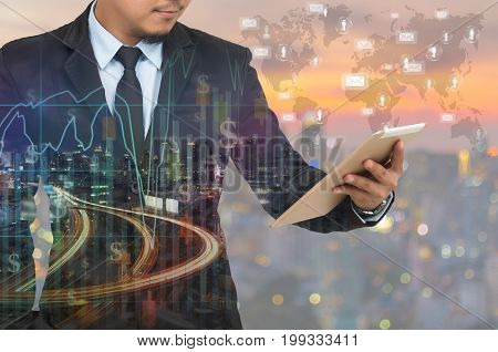 Double exposure of businessman using the tablet with cityscape and financial graph on blurred building background Elements of this image furnished by NASA Business Trading concept
