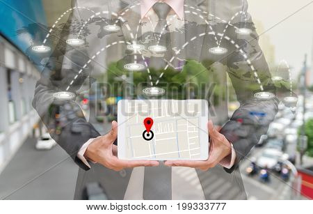 Businessman holding a tablet showing part of navigator map on connection line over the world map with blurred photo of traffic jam Navigation conceptElements of this image furnished by NASA,