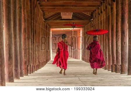 Back side of two young monk holding the traditional umbrella on the Mya Thein Tan Pagoda at bagan mandalay myanmar Buddhist novice are walking in pagodamyanmar