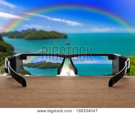 Conceptual image of landscape focused in glasses lenses over the photo blurred of Top view of Ang Thong National Marine Park with rainbow Thailand