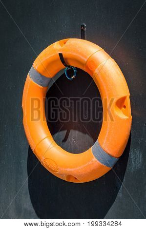 Orange lifebuoy on the dark wall near swimming pool
