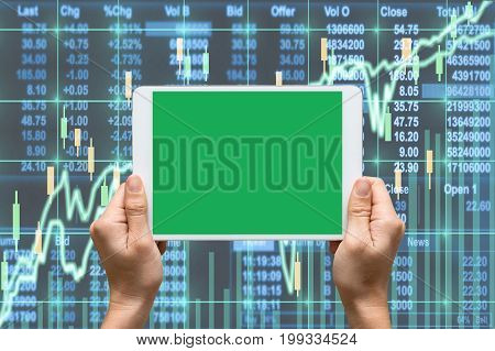 Female hand holding tablet touch screen showing green screen background for insert text and picture over the Stock market exchange data on LED displayBusiness financial and technology concept, 3D illustration