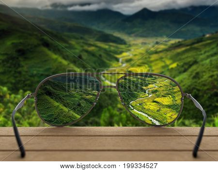 Conceptual image of Landscape focused in glasses lenses over the photo blurred of Top view point which can see Rice terraced fields background