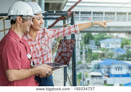 Happy professional construction engineers working with Corporate Colleagues Teamwork and technology laptop at the building site place Industrial Concept