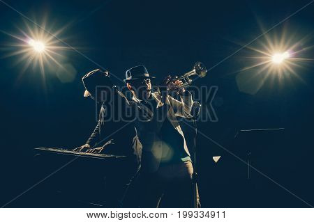 Musician Duo band playing a Trumpet and keyboard on black background with spot light and lens flare musical concept