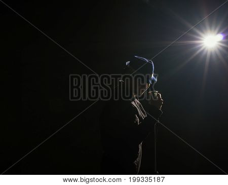 Asian Musician singing a song with microphone on black background with spot light and lens flare musical concept