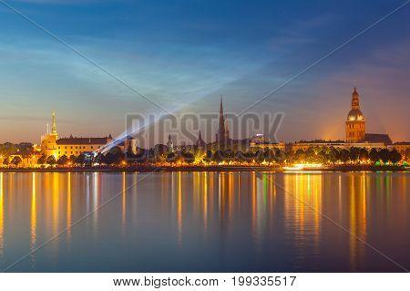 RIGA, LATVIA - 23 JUN 2016. Amazing night panorama of illuminated old town of Riga with reflection in Daugava river. Shortest night in a year, Ligo festival