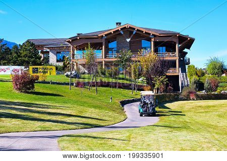 Bansko, Bulgaria - October, 31, 2015: Pirin Golf Club house and restaurant, colorful autumn trees, golf carts, path, green grass, blue sky