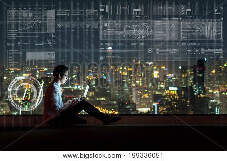 Asian businessman sitting and using the laptop showing digital virtual screen over the cityscape background at night time Business technology and innovation concept