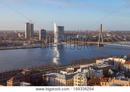RIGA, LATVIA - 25 DEC 2015. Modern bank building and cable-stayed bridge over Daugava river