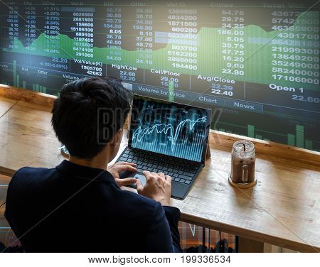 Back side of Businessman sitting and using computer laptop showing trading graph beside the windows glass over the stock market chart background Business financial and trading concept