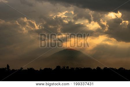 Fantastic landscape with mountain and rays of light shineDramatic sunset worm tone