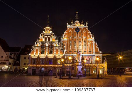 RIGA, LATVIA - 25 DEC 2015. House of the blackheads located in the old town of Riga, Latvia. Night view with dark sky in background and illuminated buildings in foreground.
