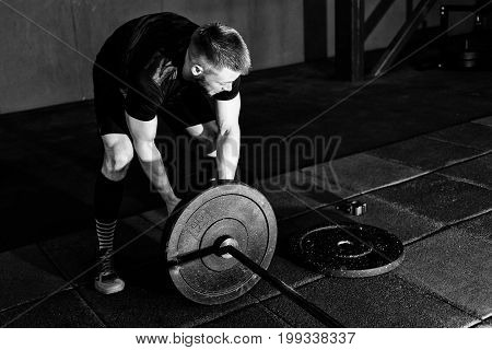 Bearded man putting weights on bar in gym. Preparing to workout with a barbell. Bodybuilder puts weights on barbell