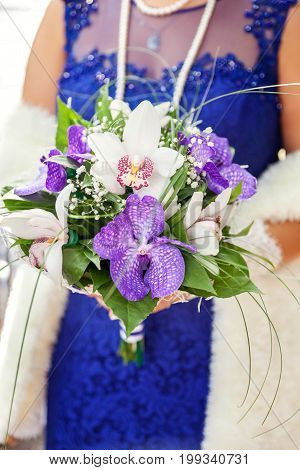 Details of the wedding dress and bride's hands ring with bouquet