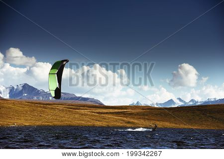 Kite surfing in lake area on background of mountains. Space for text. Altay republic. Siberia, Russia