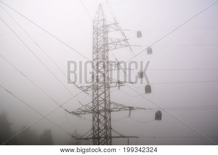 Electric high voltage power post abstract view in morning haze