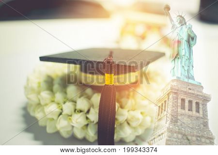 Concept of congratulate graduate study success graduation black cap on Jasmine garlandEducation certificate of Abroad international diploma or certificate with Liberty background work and traver.