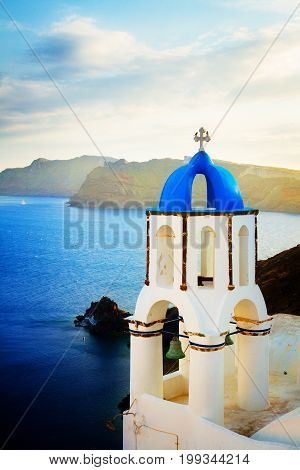 view of caldera with blue sea and belfry with blue dome, Oia, Santorini island, retro toned