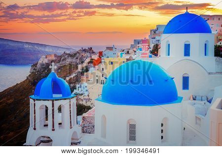 townscape of Oia, traditional greek village of Santorini, with blue domes of churches close up at sunset, Greece, retro toned