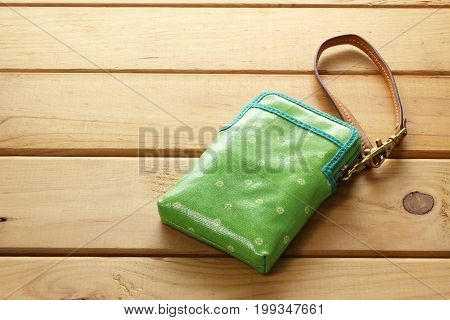 Green Purse with Straps on wooden Background