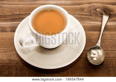 coffee in a white cup with milk and spoon with sweetener